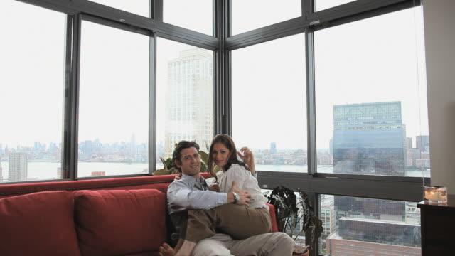 vídeos y material grabado en eventos de stock de ms portrait of couple embracing sitting on sofa, jersey city, new jersey, usa - en el regazo