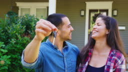 Portrait Of Couple Holding Keys To New Home On Moving In Day