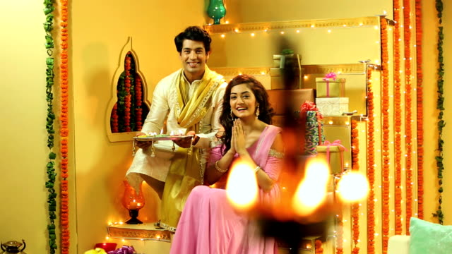 vídeos y material grabado en eventos de stock de ms pan portrait of couple sitting on staircase holding diya with hands clasped during diwali festival at home - bandeja para servir