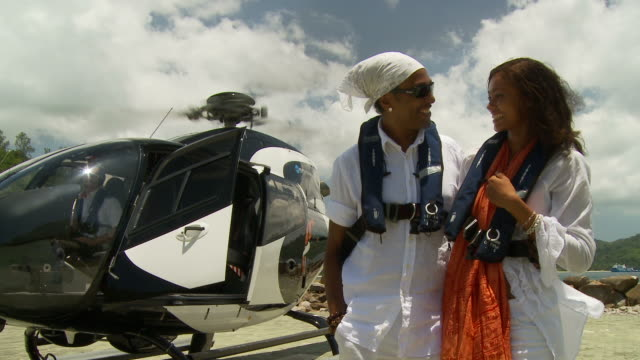 ms portrait of couple standing in front of helicopter on helipad / seychelles - helicopter tour stock videos and b-roll footage