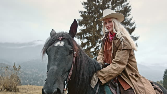 slo mo portrait of cowgirl stroking horse's neck - cowgirl stock videos & royalty-free footage