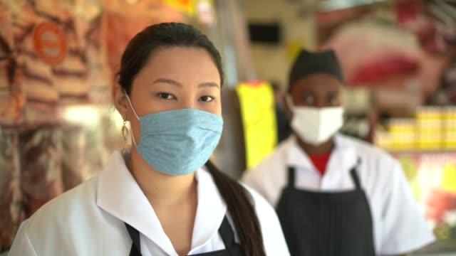 porträtt av medarbetare slaktare med ansiktsmask på slaktarens butik - 4k resolution bildbanksvideor och videomaterial från bakom kulisserna