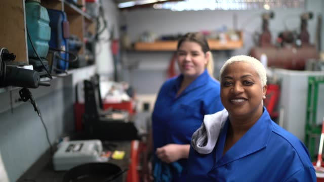 portrait of coworkers woman working in auto repair - equality stock videos & royalty-free footage
