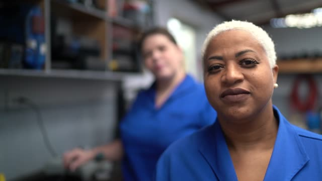 portrait of coworkers woman working in auto repair - mature adult stock videos & royalty-free footage