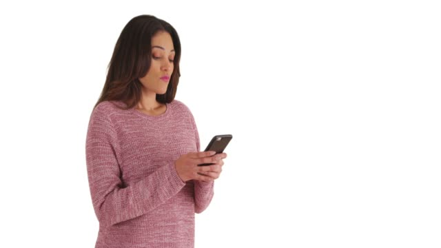 stockvideo's en b-roll-footage met portrait of cuban woman in pink sweater focused on replying to text in studio - vaste stof