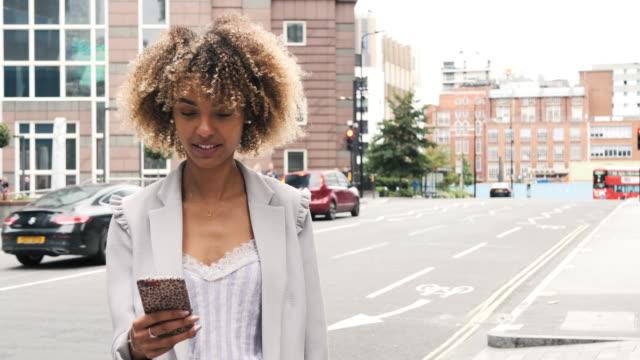 vídeos de stock, filmes e b-roll de retrato de cabelo encaracolado jovem millennial afro-americano usando celular - cabelo assanhado