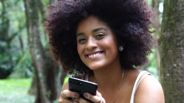 vídeos de stock e filmes b-roll de portrait of curly hair woman using mobile phone at park - mobile