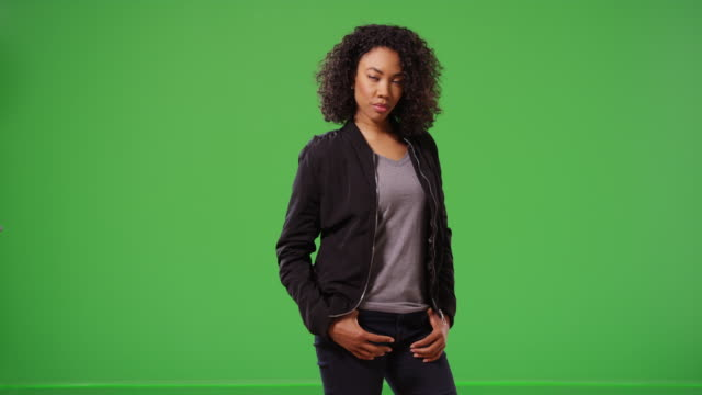 Portrait of cute black woman looking at camera with confidence on greenscreen
