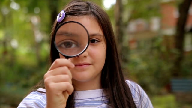 vídeos de stock e filmes b-roll de portrait of cute little girl holding magnifying glass - lupa