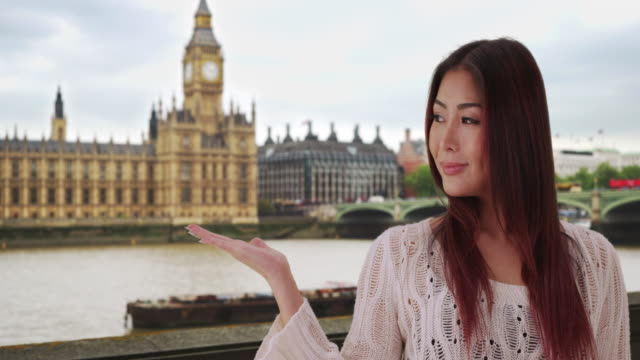 portrait of cute smiling japanese female standing near big ben clock tower - big ben点の映像素材/bロール