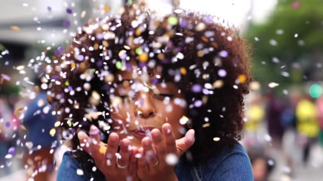 stockvideo's en b-roll-footage met portret van leuke vrouw waait confetti - multi coloured