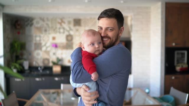 vídeos de stock, filmes e b-roll de retrato do pai segurando seu filho em casa - olhos azuis