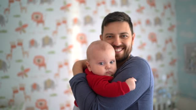 portrait of dad holding his son at home - genderblend stock videos & royalty-free footage