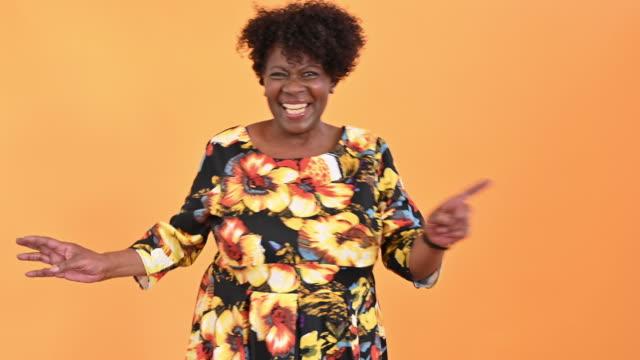 portrait of dancing senior black woman in print dress - orange background stock videos & royalty-free footage