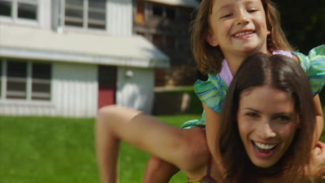 cu portrait of daughter (4-5) jumping on mother's shoulders, bovina center, new york, usa - piggyback stock videos & royalty-free footage
