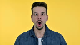 Portrait of Disappointed Young Man Feeling Shocked, Yellow Background
