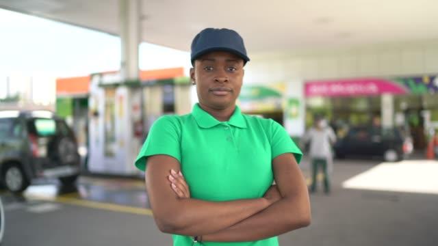 vídeos de stock e filmes b-roll de portrait of displeased female gas station attendant at work - frentista