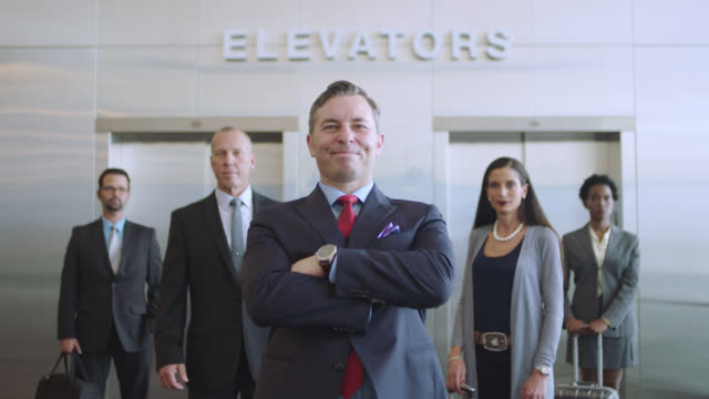 slo mo. portrait of diverse business-class travelers in front of elevators. tilt up. - chief executive officer stock videos & royalty-free footage