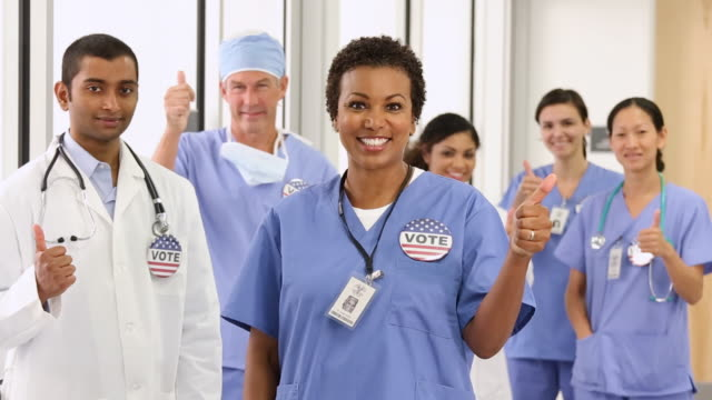 MS PAN Portrait of Diverse Group of Medical Workers Wearing VOTE Pins and Giving Thumbs Up / Richmond, Virginia, USA