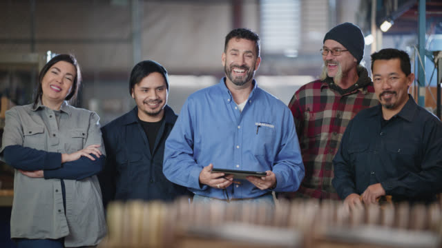 slo mo portrait of diverse group of warehouse workers laughing and smiling - five people stock-videos und b-roll-filmmaterial