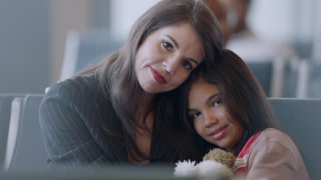 portrait of diverse mother and daughter seated in airport waiting area. - pacific islander portrait stock videos & royalty-free footage