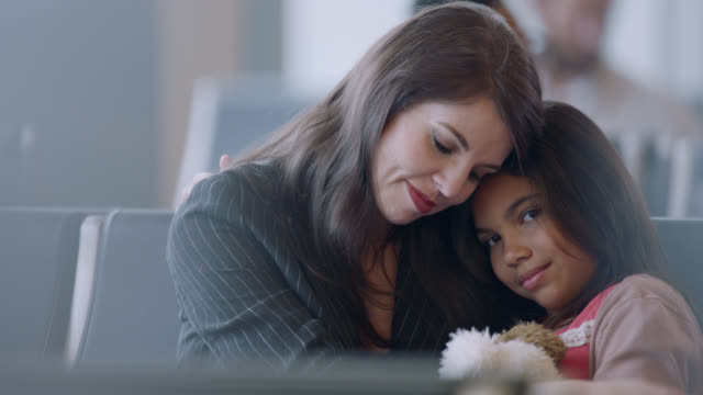 portrait of diverse mother and daughter with arms around each other seated in airport waiting area. - pacific islander family stock videos & royalty-free footage