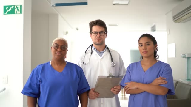 portrait of doctor and nurses at hospital - team photo stock videos & royalty-free footage