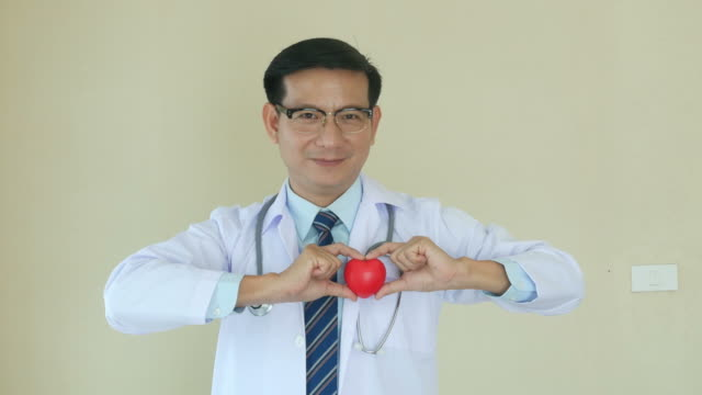 portrait of doctor in face expression , showing red heart ball