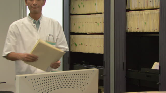 ms portrait of doctor looking at files in medical office / helmond, north brabant, netherlands - ナースステーション点の映像素材/bロール