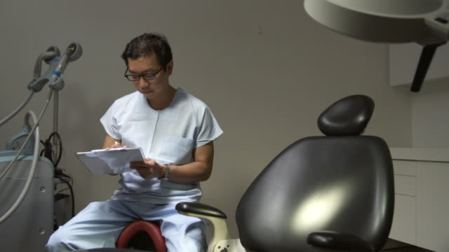 ms, portrait of doctor sitting next to empty operating chair and filling out chart on clipboard, sydney, australia - clinic stock videos & royalty-free footage