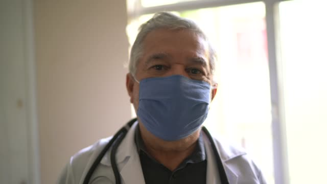 portrait of doctor wearing protective face mask - 65 69 anni video stock e b–roll