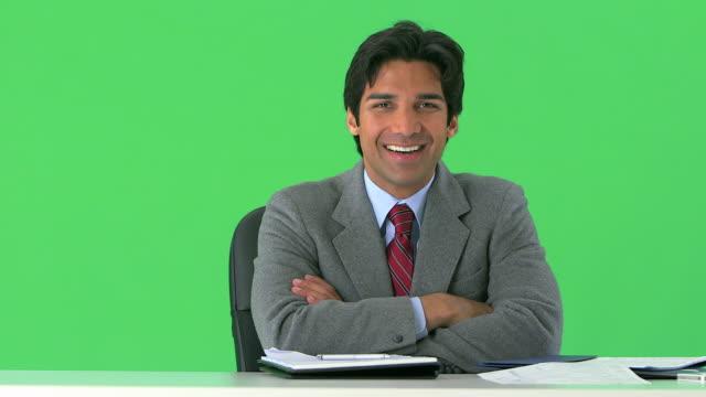 vidéos et rushes de portrait of east indian businessman smiling at desk on greenscreen - assis