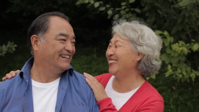 CU Portrait of elderly couple laughing together in park / China