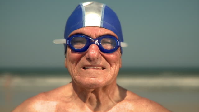 slo mo cu portrait of elderly man wearing swimming cap and goggles standing on beach, jacksonville, florida, usa - swimming goggles stock videos & royalty-free footage