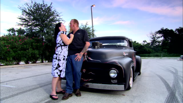 ms ,portrait of embracing couple standing by vintage car on parking lot, jacksonville, florida, usa - see other clips from this shoot 1403 stock videos and b-roll footage