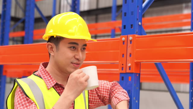 portrait of employee man working in warehouse store , resting and drinking coffee - coffee break stock videos & royalty-free footage