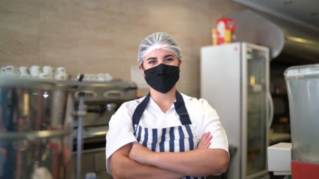 vídeos de stock, filmes e b-roll de retrato de funcionário seving café com máscara facial - braços cruzados