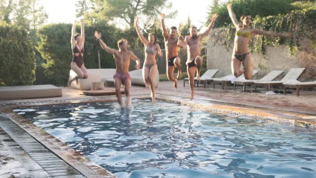 vidéos et rushes de verticale des amis espagnols énergiques sautant dans la piscine - vue de face