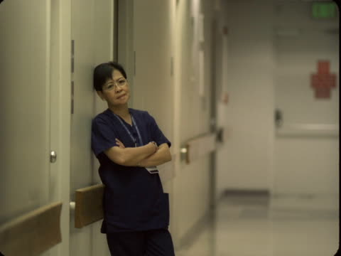 ms, portrait of exhausted female doctor leaning against wall in hospital corridor, reno, nevada, usa - leaning stock videos & royalty-free footage