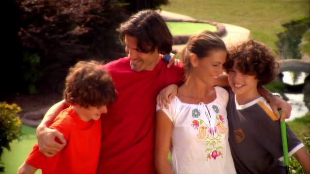 portrait of family at mini golf course - minigolf stock-videos und b-roll-filmmaterial