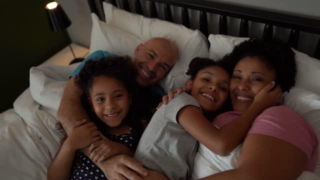 vídeos de stock, filmes e b-roll de retrato da família na cama em casa - miscigenado