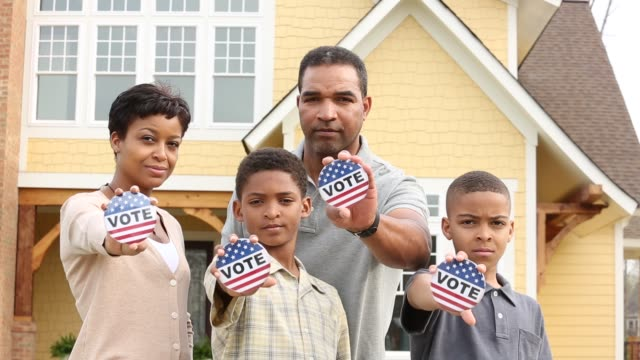 MS Portrait of family in front of home holding vote campaign buttons