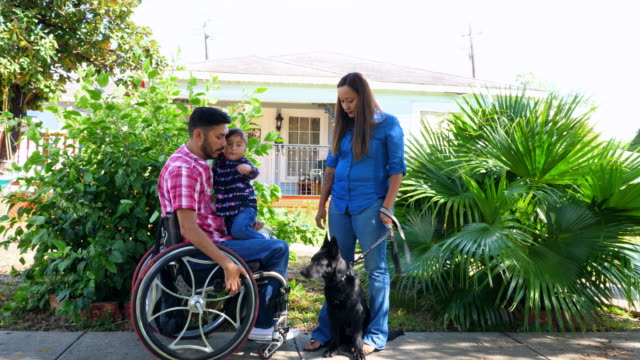 vídeos y material grabado en eventos de stock de ms portrait of family in front of home with daughter sitting in fathers lap in wheelchair - animal family