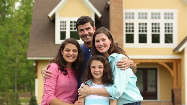 portrait of family in front of new suburban home - stereotypically middle class stock videos & royalty-free footage