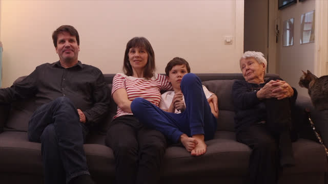 march 04: portrait of family members sitting on sofa watching press conference of jean castex and olivier veran broadcast by french tv channel france... - multi generation family stock videos & royalty-free footage