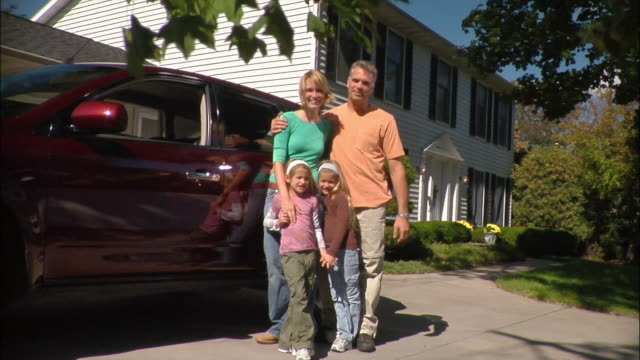 Portrait of family of four standing next to car in driveway