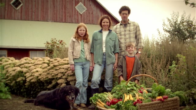vídeos de stock e filmes b-roll de portrait of family of organic farmers posing with dog and basket of fresh produce in front of barn - agricultor