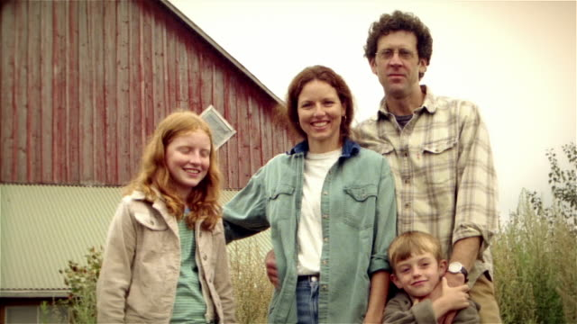 portrait of family on family farm / boy frowning at first then smiling - family portrait stock videos & royalty-free footage