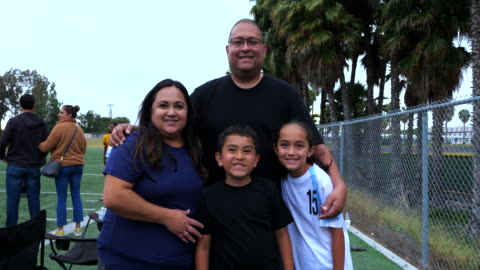 ms portrait of family on sidelines of soccer field after watching daughter play - jeans stock videos & royalty-free footage