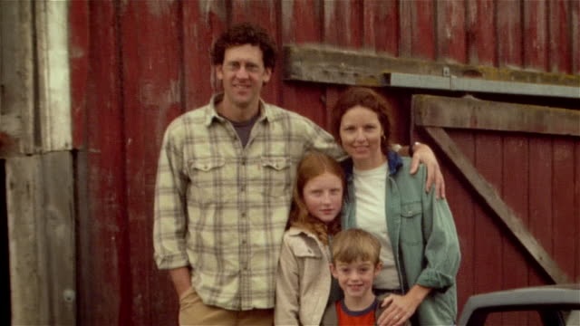 Portrait of family posing in front of red barn